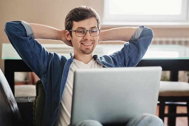 Счастливый фрилансер в очках, используя ноутбук для удаленной работы, сидя на диване у себя дома