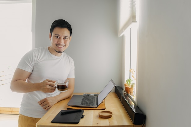 Happy freelancer man is working on his laptop. concept of freelance creative works.