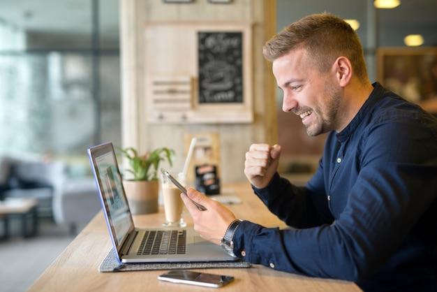 Счастливый фрилансер с планшетом и портативным компьютером в кафе