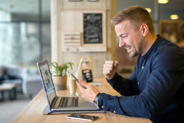 Happy freelancer with tablet and laptop computer in coffee shop