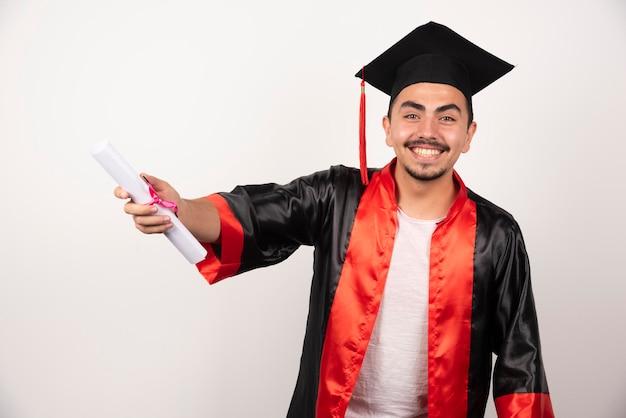 白でポーズをとる卒業証書を持つ幸せな新卒者。