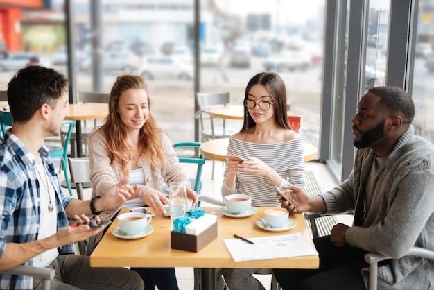 С днем пятницы. группа симпатичных иностранных студентов сидят в кафетерии с кофе и мило беседуют.