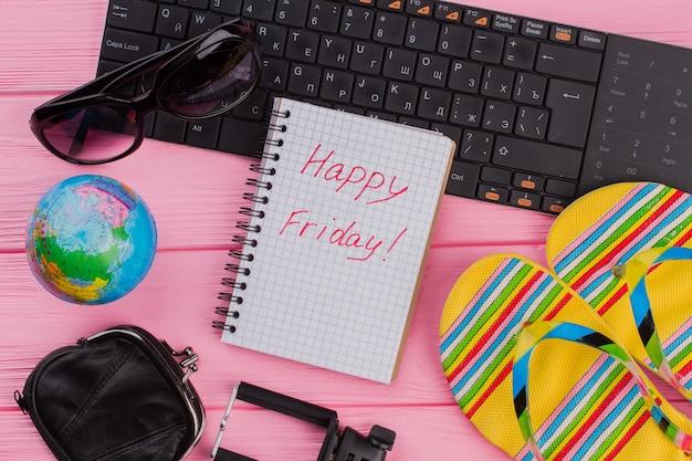 ピンクのテーブルトップの背景に女性の旅行者アクセサリーメガネ財布とビーチサンダルとノートブックであなた自身の幸せな金曜日。グローブと黒のキーボード。