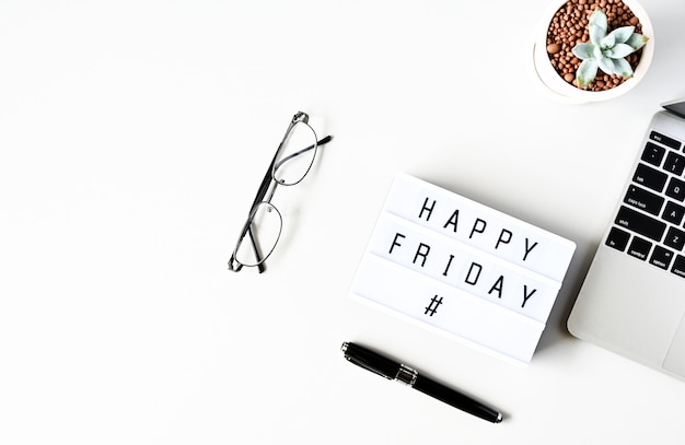 Happy friday text on lightbox composition on white table