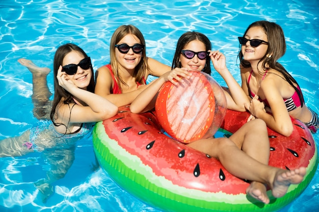 Happy friend girls in swimming pool