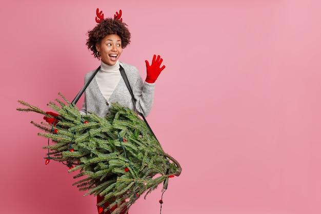 La donna afroamericana felice e amichevole incontra il migliore amico sulla festa di capodanno sciocchi intorno tiene l'albero di abete di natale verde come se la chitarra finge di essere un cantante rock professionista pone uno spazio vuoto al coperto