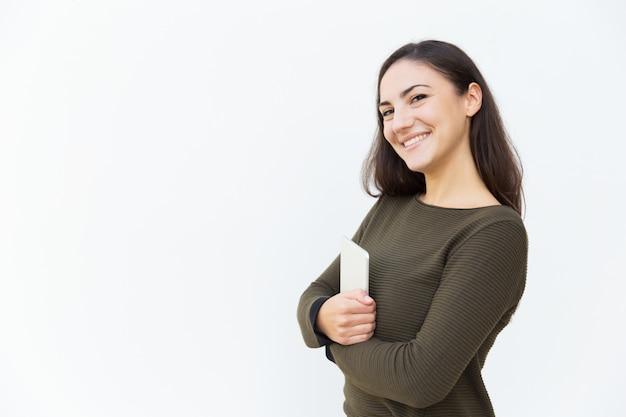 Bella donna latina amichevole felice che posa con la compressa
