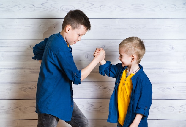 Happy and friendly brothers during the game of arm wrestling. two positive friends fighting by hands