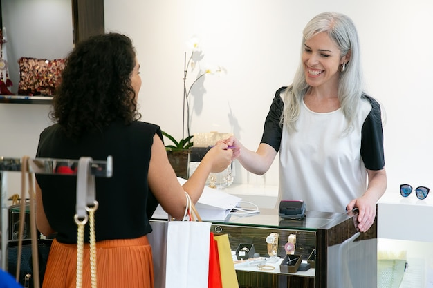구매, 채팅, 미소 및 웃음에 대한 지불을 위해 고객으로부터 신용 카드를 복용하는 행복 친절한 점원. 미디엄 샷. 쇼핑 컨셉
