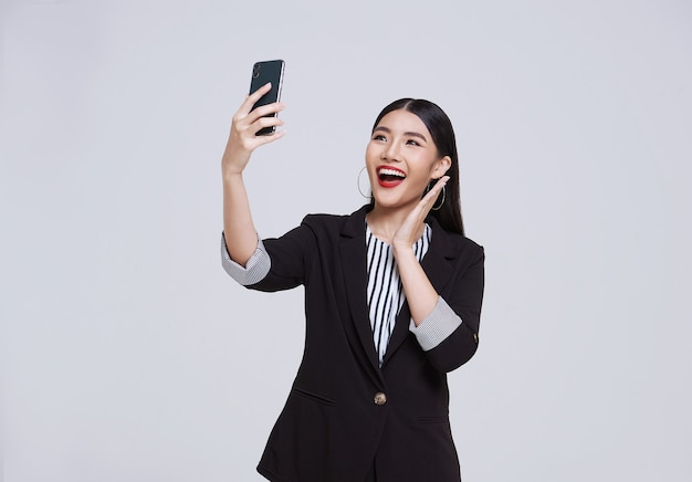 Happy and friendly face asian businesswoman smile in formal suit her using smartphone has a video call on white background studio shot.