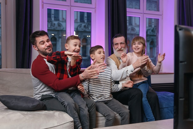 Happy friendly family watching football match, championship on the couch at home. fans emotional cheering for favourite national team. daddy, grandpa and grandchildren. sport, tv, having fun.