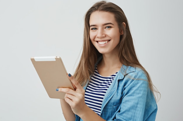 Happy friendly gorgeous female assistant smiling broadly holding digital tablet, posing joyfully, satisfied how easy draw using gadget