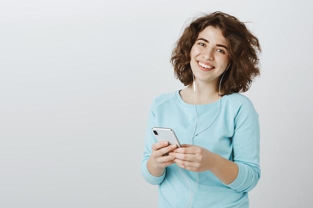 イヤホンで音楽を聴きながら携帯電話を使用しながら笑って幸せな優しい女の子