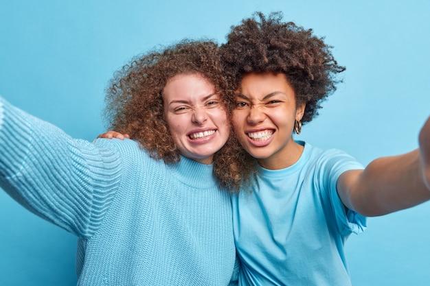 행복 친화적 인 혼혈 젊은 여성이 치아와 함께 셀카 미소에 대한 ans 포즈를 포용하면 파란색 벽에 부담없이 고립 된 옷을 입은 건방진 표정이 있습니다. 사람들의 감정 재미 우정 개념