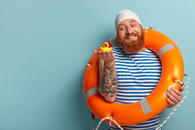 L'uomo dai capelli rossi amichevole felice tiene l'anatroccolo giallo di gomma, gode di nuotare nel mare durante la calda giornata estiva