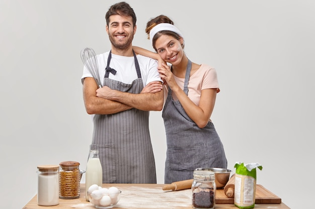 Happy friendly team of professional chefs pose together at kitchen, satisfied with good work, prepare meal, stand next to each other, use different ingredients bake confectionery for breakfast at home