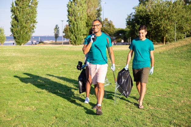 Happy friendly volunteers carrying litter