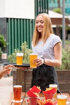 Счастливая дружелюбная официантка, подающая пинты лагера или пива в ресторане на открытом воздухе, улыбается, когда покупатель протягивает руку, чтобы взять бокал