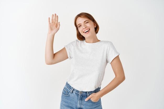 행복한 친절한 여성이 손을 흔들며 인사하고, 웃고 인사하고, 흰 벽에 기대어 서 있는 안녕 제스처