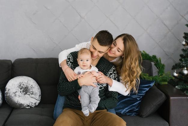 クリスマスツリーでソファに座っている小さな子供の息子と幸せなフレンドリーな若い家族。彼らは抱擁と笑顔