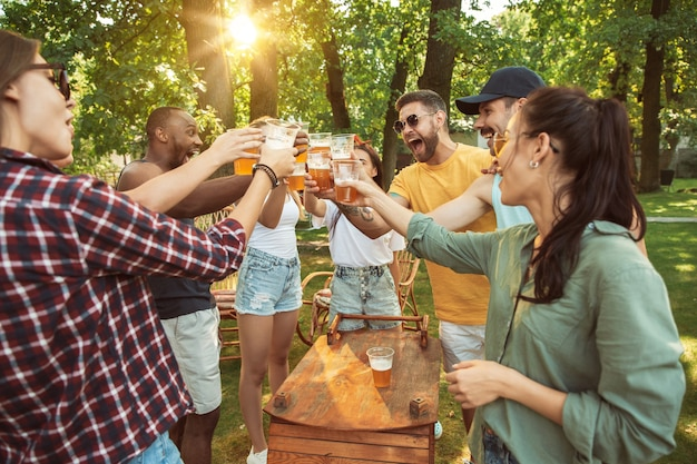 Счастливые друзья пьют пиво и барбекю в солнечный день