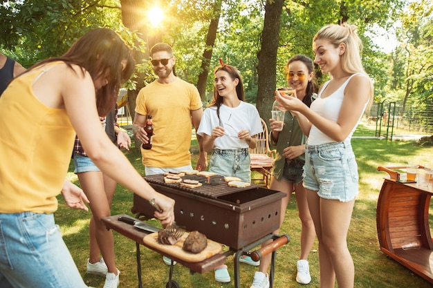 幸せな友達は晴れた日にビールとバーベキューパーティーをしています