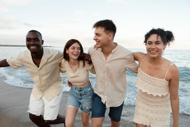 해변 미디엄 샷에서 행복한 친구