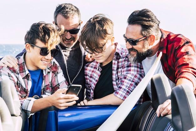 Счастливые друзья на пляже готовятся к серфингу - пара подростков разговаривает и смеется в машине, а двое взрослых смотрят на один телефон