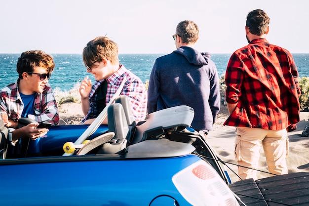 Счастливые друзья на пляже готовятся отправиться на серфинг - пара подростков разговаривает и смеется в машине, а двое взрослых смотрят на море