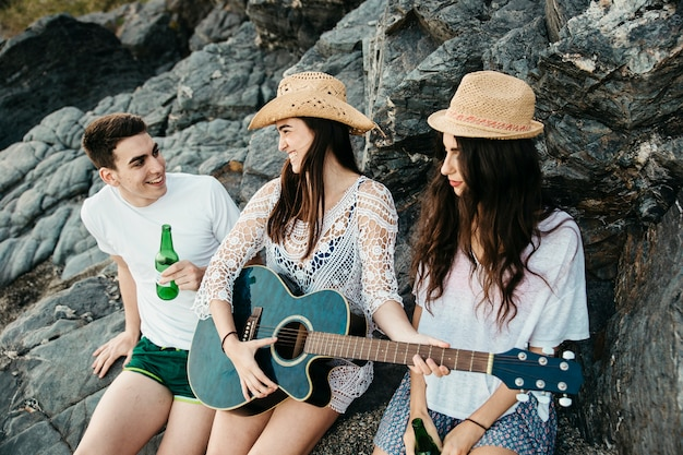 Happy friends at the beach with guitar