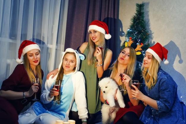 家で5人の美しい女の子と一緒にクリスマスや新年を祝って乾杯する幸せな友達