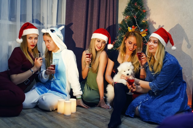 シャンパンと乾杯のグラスでクリスマスや新年を祝う幸せな友達。家でクリスマスを祝う5人の美しい女の子