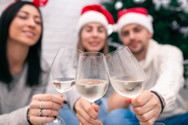 Happy friends celebrating new year in home interior in christmas hats sitting near a christmas tree with glasses of wine. wine glasses are the focus. blurred figures of people behind glasses