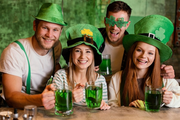 Happy friends celebrating together st. patrick's day at the bar