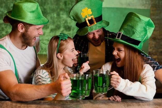 Amici felici che celebrano insieme st. patrick's day con drink al bar