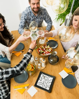 Happy friends clinking wine glasses