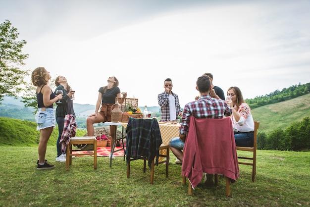 Счастливые друзья делают барбекю на открытом воздухе