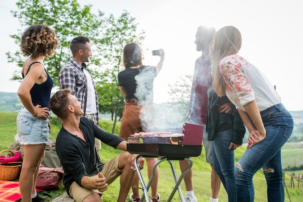 Happy friends doing barbecue outdoors
