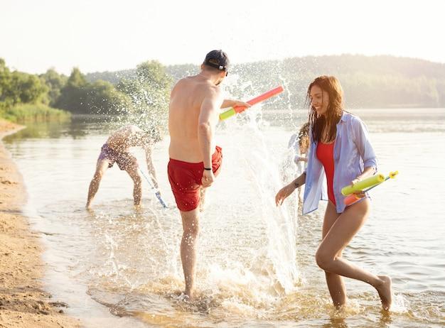 水鉄砲との戦いをしている幸せな友達-若者、夏のライフスタイルと休日のコンセプト