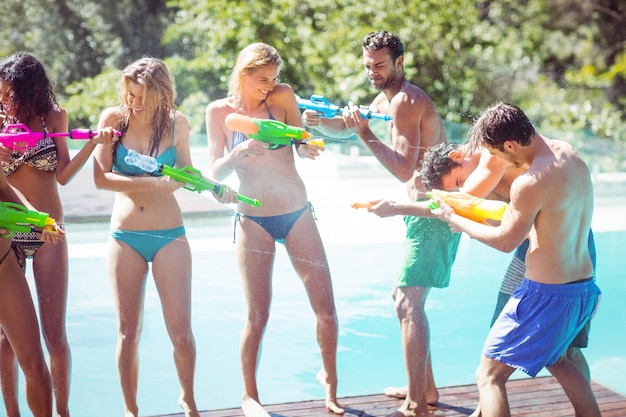 Happy friends doing water gun battle poolside