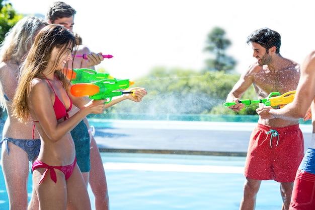 Счастливые друзья сражаются с водяной пушкой