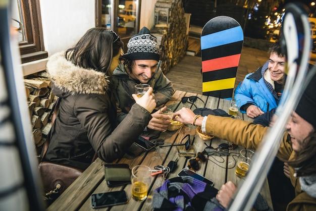 Apresスキーでビールを飲み、チップを食べる幸せな友達