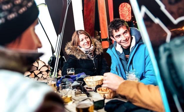 Счастливые друзья пьют пиво и едят чипсы в апрески на открытом воздухе