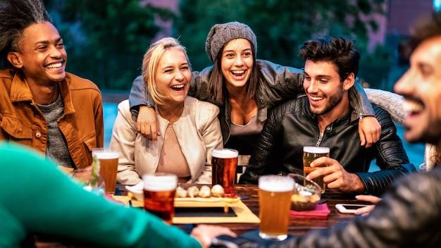 양조장 바 dehor에서 맥주를 마시는 행복 한 친구