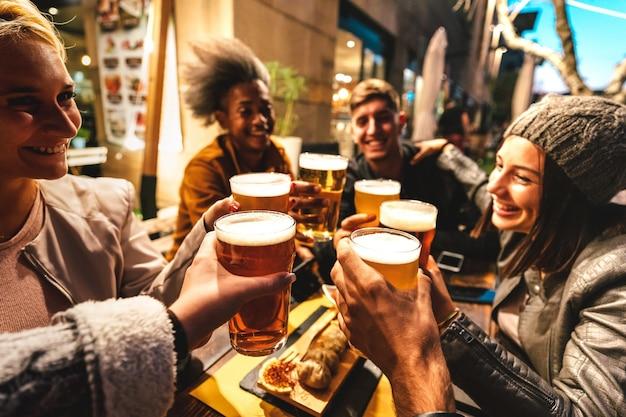 Счастливые друзья пьют пиво в баре-пивоварне на открытом воздухе в ночном настроении