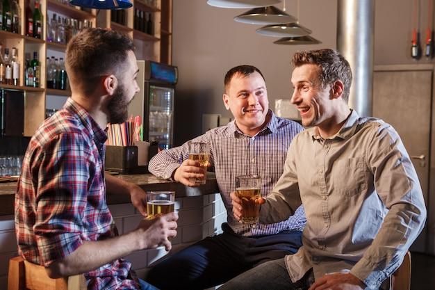 Счастливые друзья пили пиво на прилавке в пабе