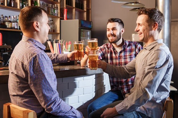 Happy friends drinking beer at counter in pub