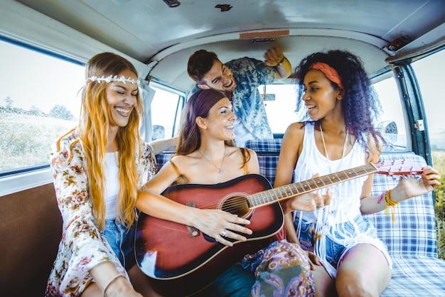 Happy friends driving a vintage minivan