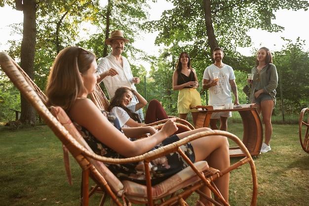 Счастливые друзья едят и пьют пиво на ужине-барбекю во время заката