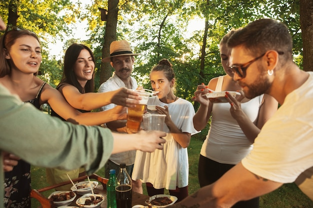 日没時間のバーベキューディナーでビールを食べたり飲んだりして幸せな友達